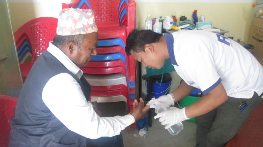Krishna Bahadur Pariyar having his finger treated by a health worker