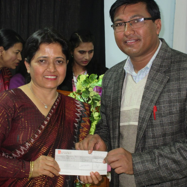 RMF Program Manager handing the scholarship amount over to BMS Coordinator Binda Ghimire