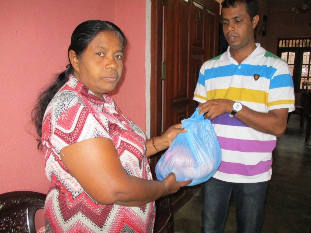 Madura's mother receives the food parcel from Nishantha