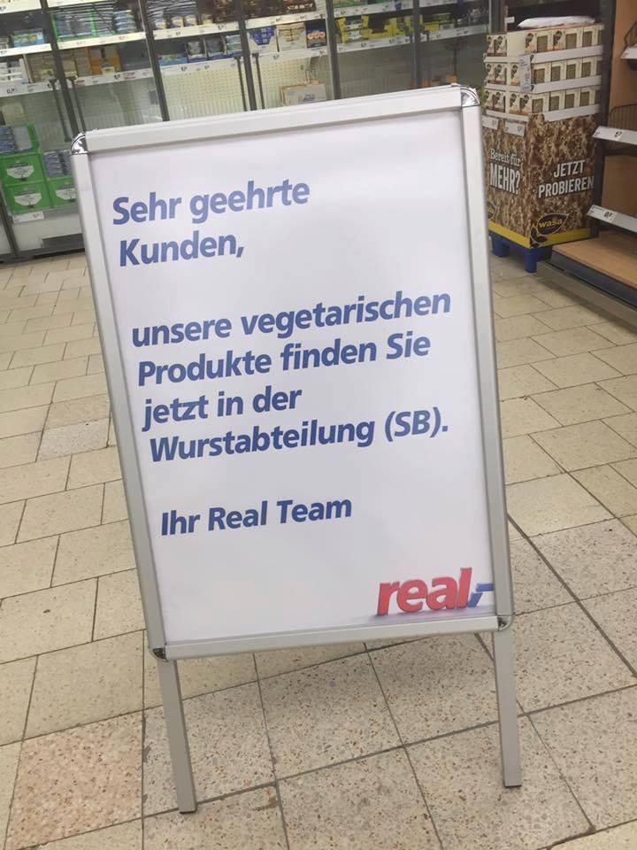 """Schild bei """"real"""", auf dem steht: """"Sehr geehrte Kunden, unsere vegetarischen Produkte finden Sie jetzt in der Wurstabteilung. Ihr Real-Team"""""""