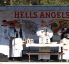 """Katholische Priester auf einer Bühne in Polen - hinter ihnen ein Plakat mit der Aufschrift """"Hells Angels"""""""