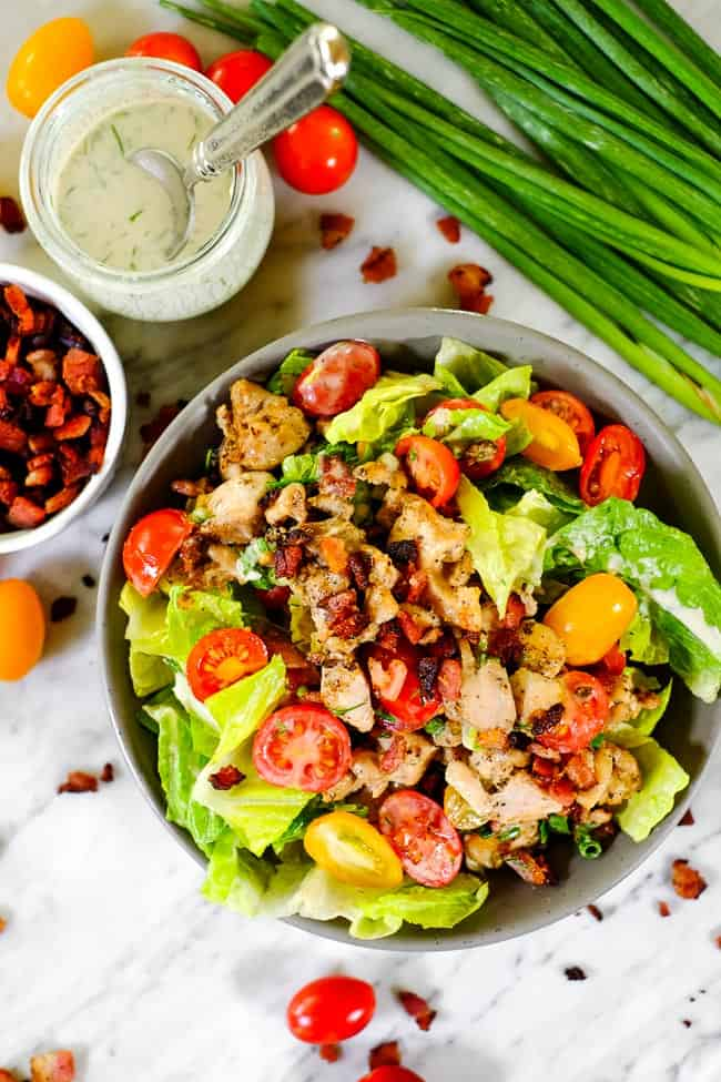 BLT salad in a bowl with tomatoes, bacon, dressing an green onion garnish.