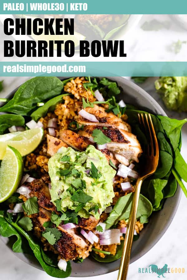 Close up of chicken burrito bowl, topped with chopped red onion, guacamole, cilantro and lime wedges in a bowl with a fork. Long pin for pinterest.