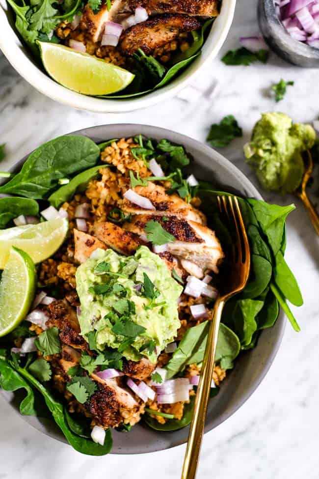 Chicken burrito bowl served up with chopped red onion, guacamole, cilantro and lime wedges in a bowl with fork.