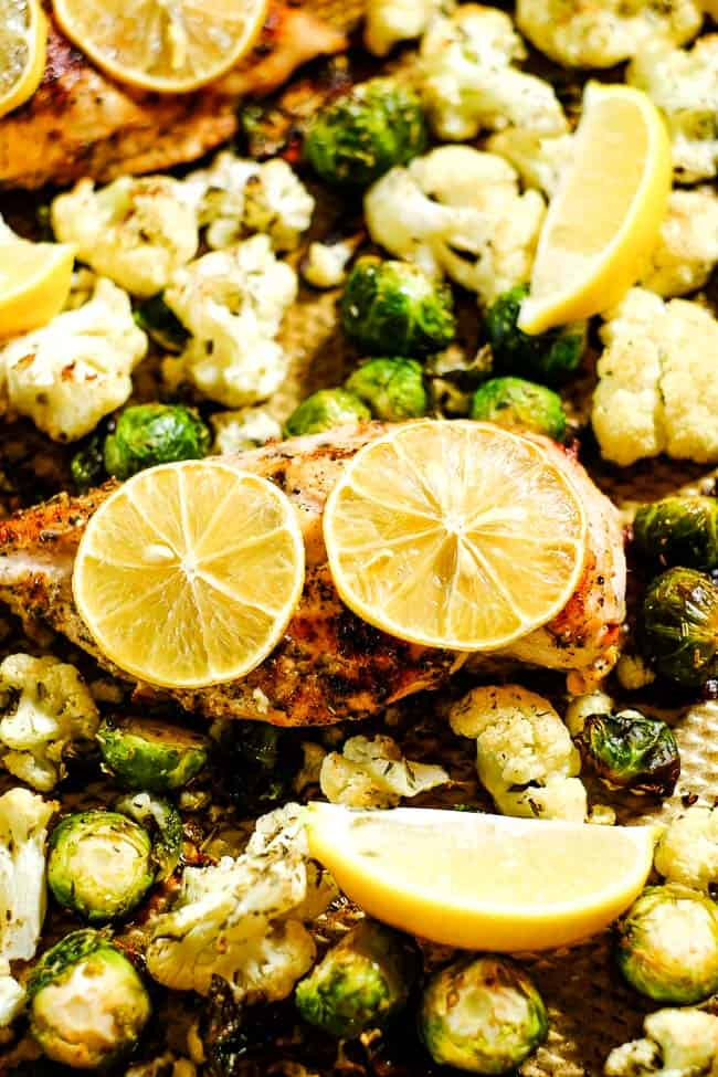 Close up angled shot of easy lemon chicken and roasted brussels and cauliflower on sheet pan with lemon slices.