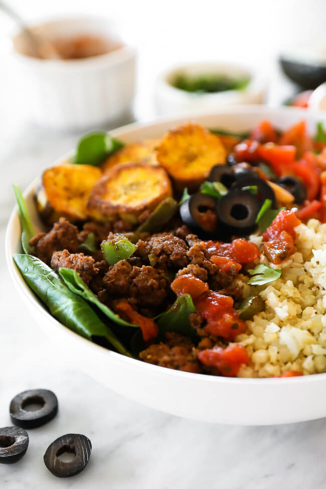Angled close up image of ground beef taco bowl served with cauliflower rice, tomatoes, olives, salsa, fried plantains, avocado and chopped cilantro.