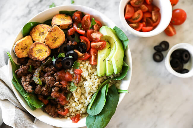 Ground beef taco bowl served with cauliflower rice, tomatoes, olives, salsa, fried plantains, avocado and chopped cilantro.