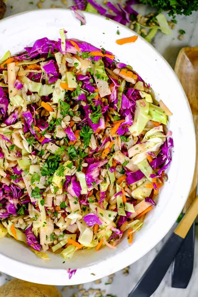 Healthy coleslaw in a serving bowl with serving utensils on table along with slaw ingredients.