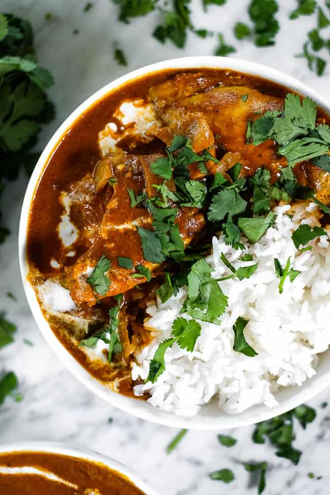 Instant pot butter chicken in a bowl served with white rice. Topped with a drizzle of coconut milk and fresh chopped cilantro.