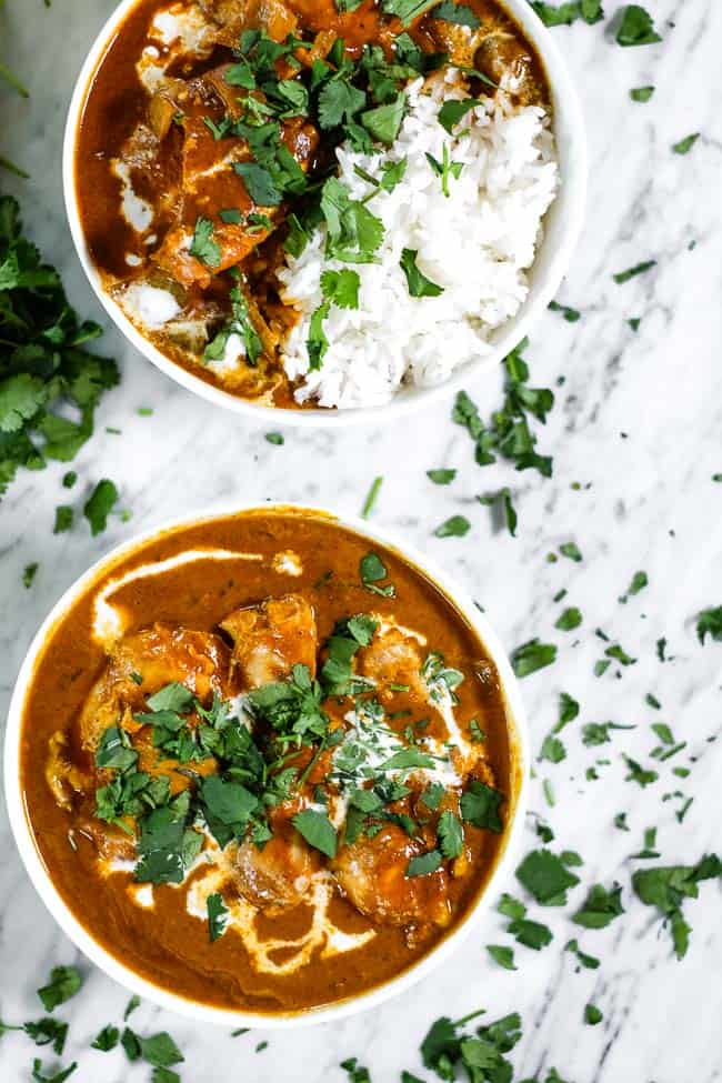Instant pot butter chicken in two bowls one with white rice. Both bowls topped with coconut milk and chopped fresh cilantro.