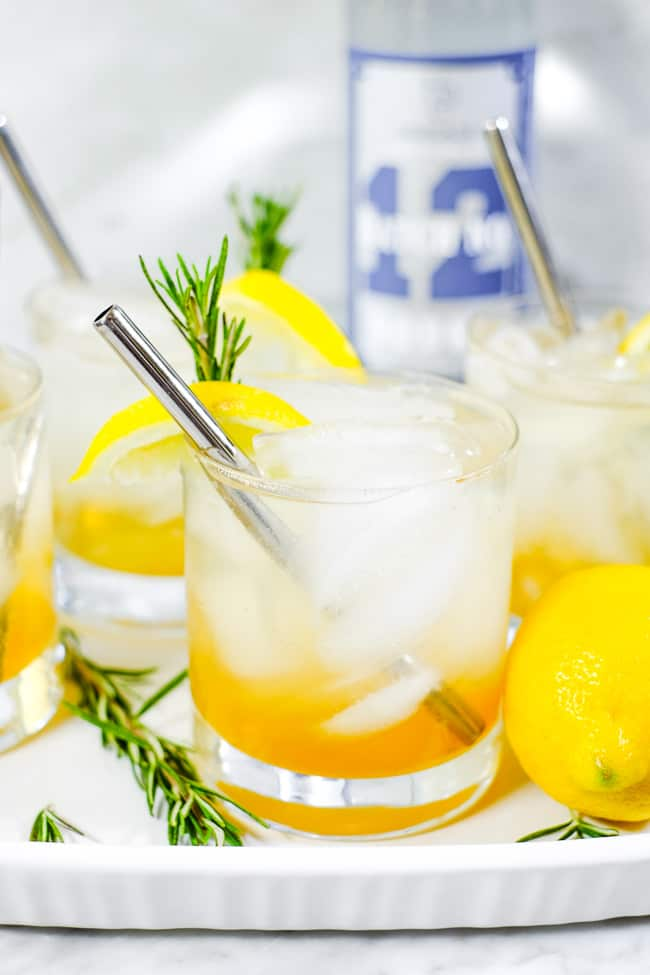 Tray with four glasses of iced lemon & rosemary cocktail with lemon wedges, fresh rosemary and stainless steel straws.