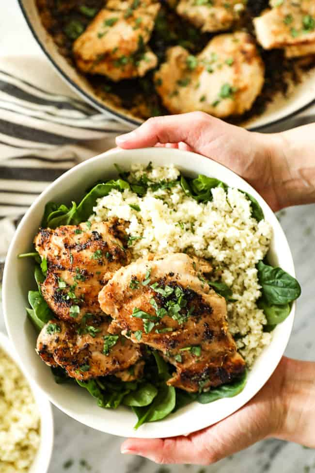 Image of holding a bowl with greens, cauliflower rice and lemongrass chicken with chopped cilantro on top.