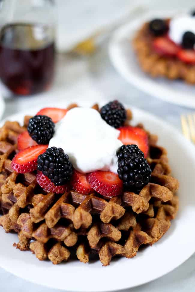 Stack of Paleo waffles topped with berries and coconut whipped cream.