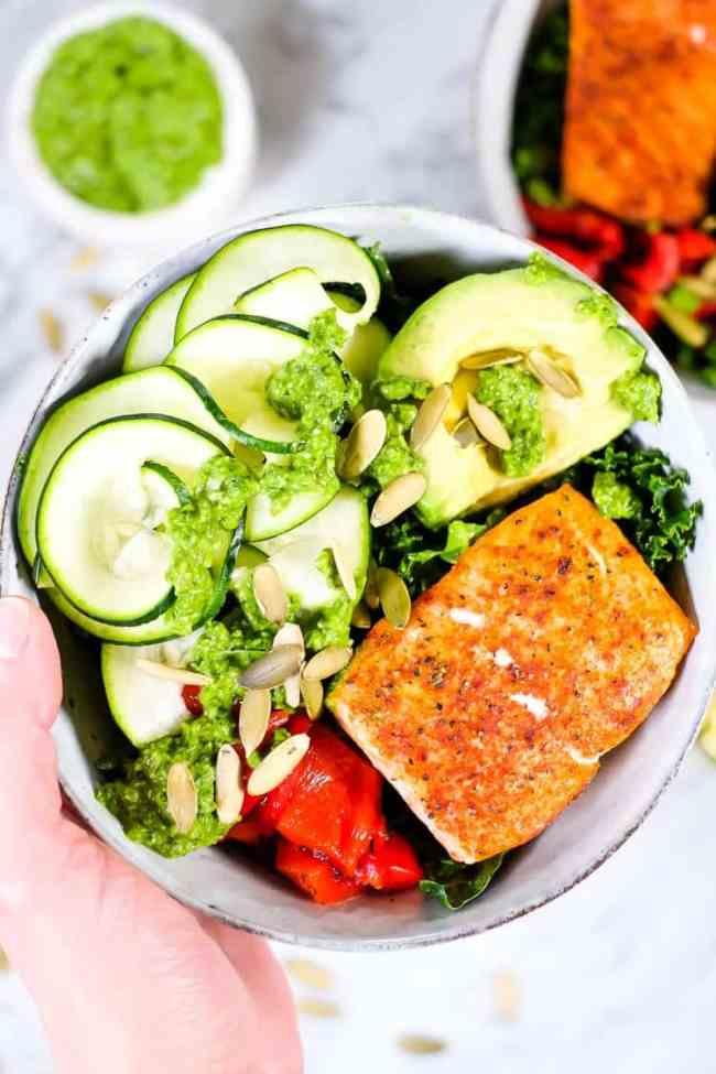 Salmon pesto kale veggie bowl with pesto sauce and pumpkin seeds close up shot