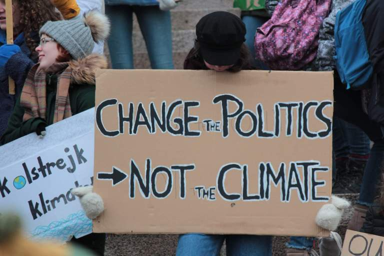 Person holding a plaque card: Change Politics, Not Climate