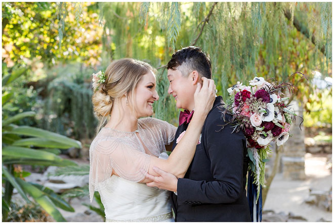 Bride and Bride hold each other face to face in a garden.