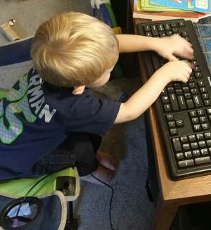 literacy station at home: 2 year old typing on an unplugged keyboard