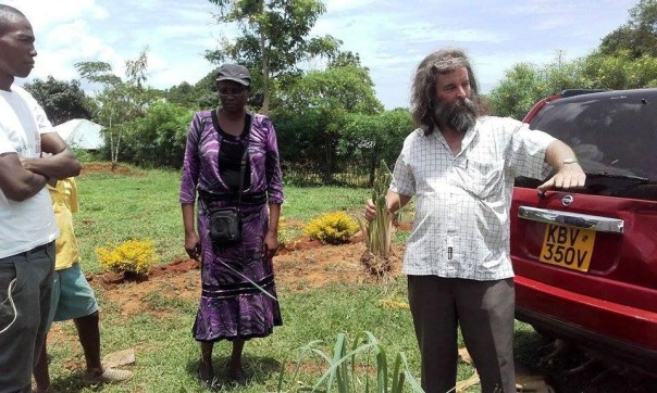 Photo of Roger explaining about planting Vetiver Grass to the youth, with Margaret Oluoch looking on