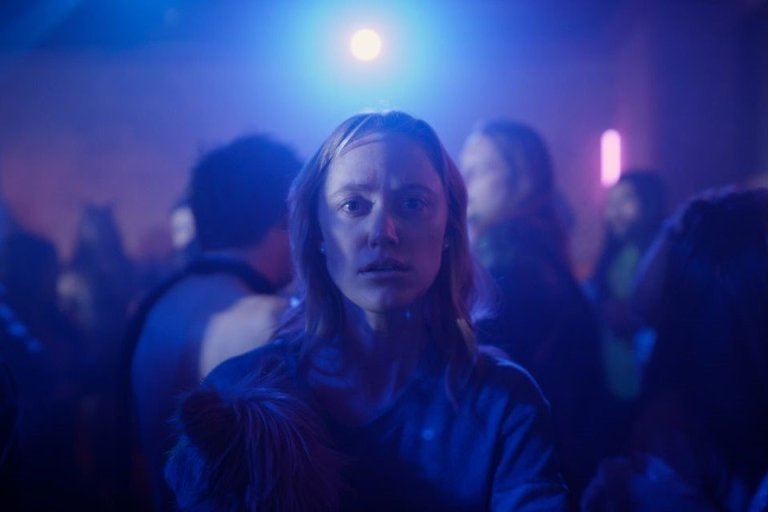 Clare holds her dog in a nightclub in Quibi's THE STRANGER Part 8.