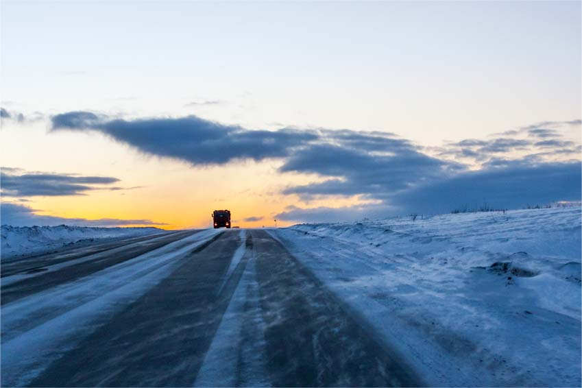 A lonely trucker driving in the blizzard at the dusk