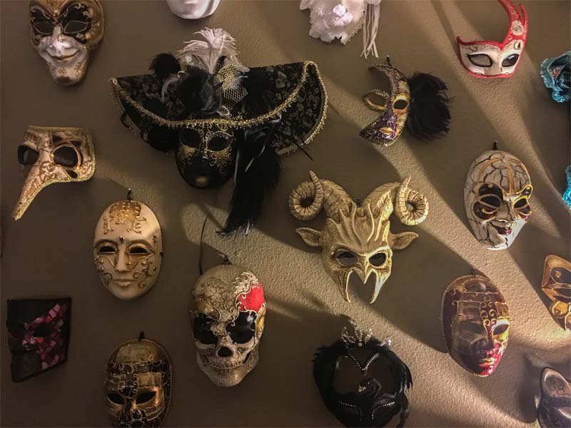 Collection of masquerade masks hang on a home's wall