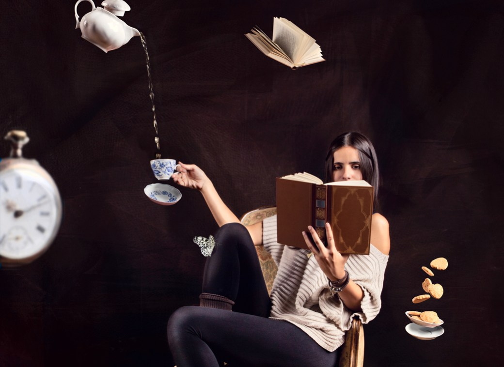 Woman reading book with abstract flying items around her