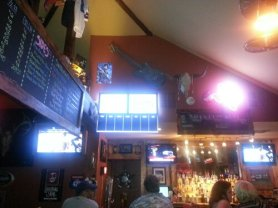 Flat screen TVs show the game.