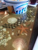 How cool is this? Seashells and beach sand are layered under the table tops.
