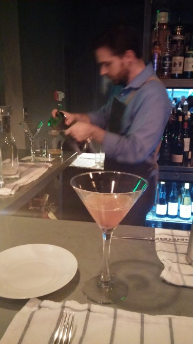 The bartender whips up smooth libations and entertains guests.