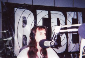 Andy Gehron with long hair, on the air at Rebel Radio