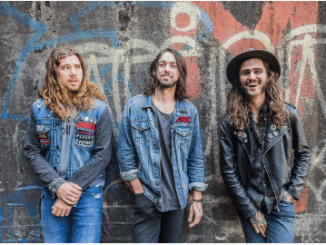 Them Evils band members (3 long-haired guys) leaning up against a painted wall