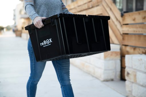Woman carrying plastic moving box with ergonomic no-rip handles while celebrating her eco-friendly choice