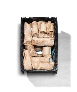 recycled plastic moving box containing kitchen items packed with honeycomb packing paper instead of bubble wrap