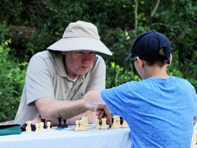 Jonathan Whitcomb plays chess with a child