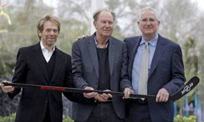 In this April 11, 2018, file photo, part-owners Jerry Bruckheimer, left, and David Bonderman pose with Tod Leiweke and a hockey stick during a news conference naming Leiweke as the president and CEO for a prospective NHL expansion team in Seattle.