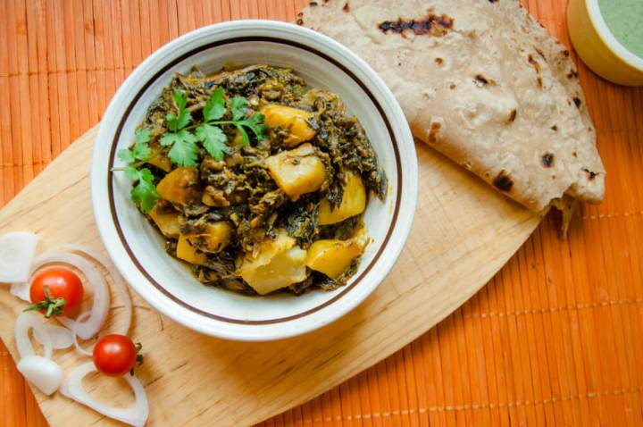 Delicious aloo palak served in a bowl with roti, raita and salad.