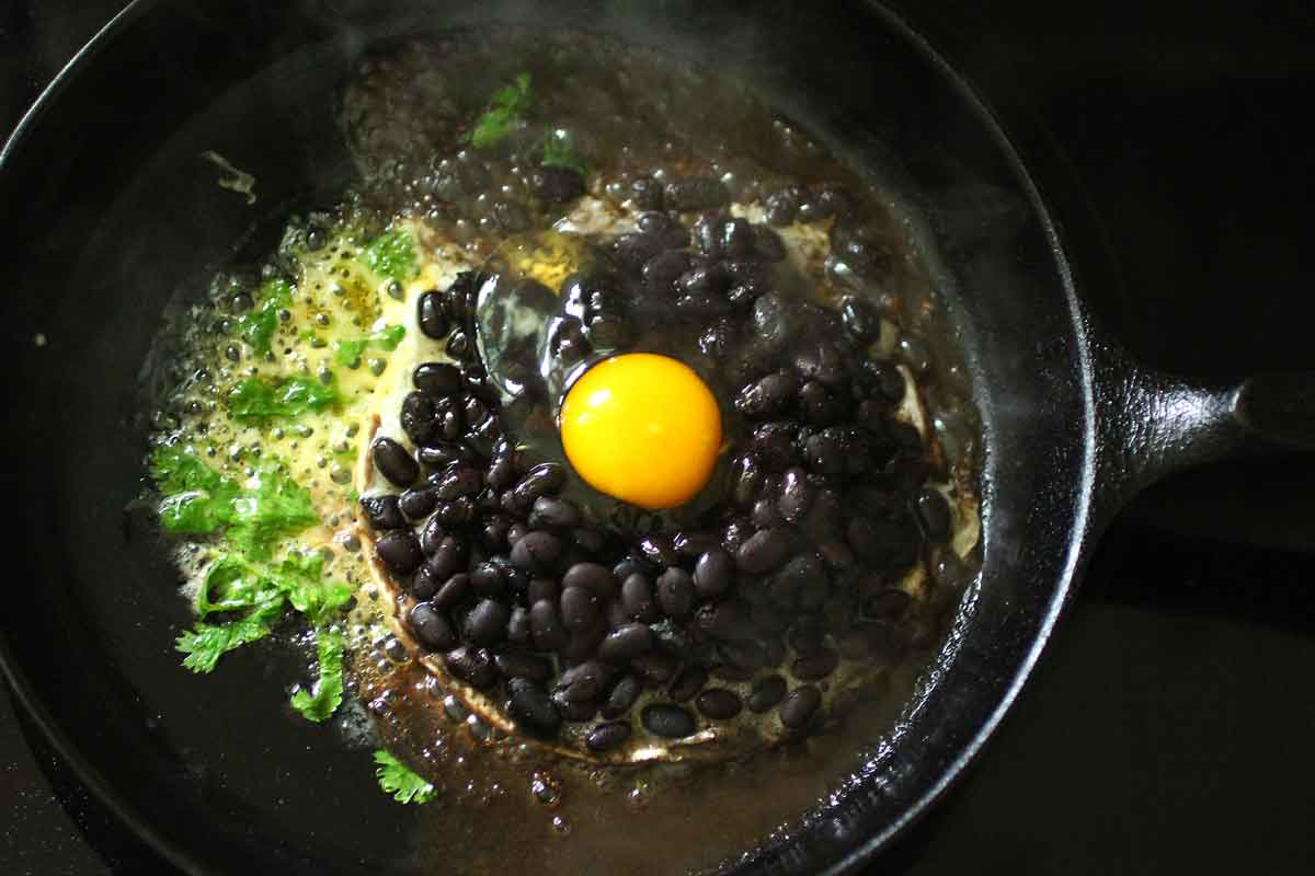 Crispy Cheesy Black Bean Breakfast cooking in the cast iron skillet