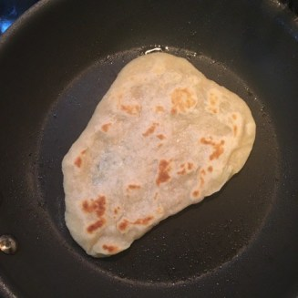 Cooking naan bread in the skillet