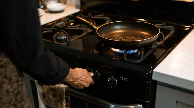 crop faceless woman adjusting rotary switch of stove