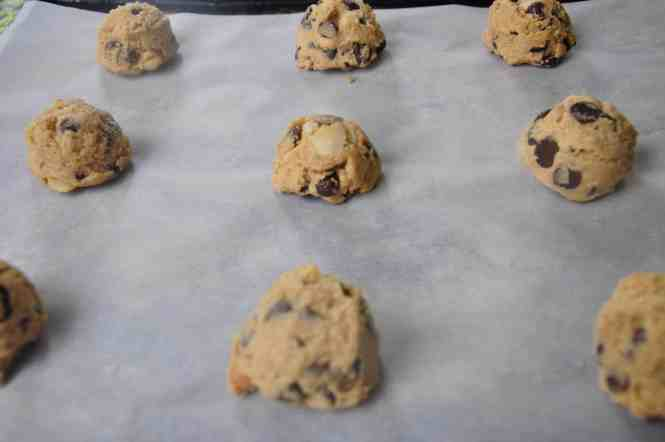 Silver baking tray with parchment paper lining dotted with Chocolate chip cookies with macadamia nuts ready for cooking