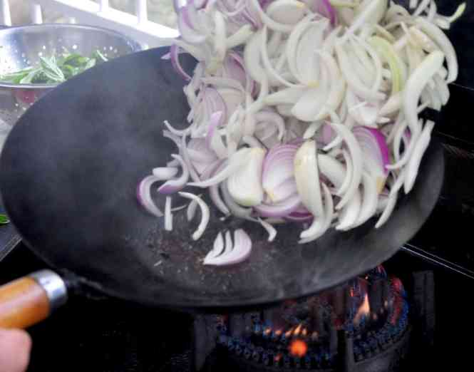 Onions being tossed in wok over gas ring