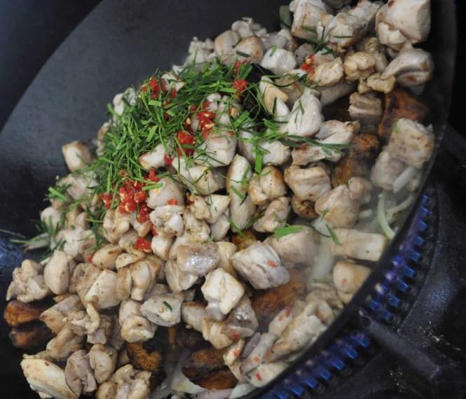 stir frying sweet potato, onions, chilli, kaffir lime leaves, kekap manis and fish sauce in wok over gas flame