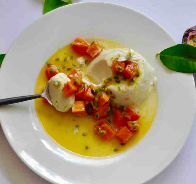 coconut and kaffir lime panna cotta with papaya and passionfruit served on a white plate with a spoon