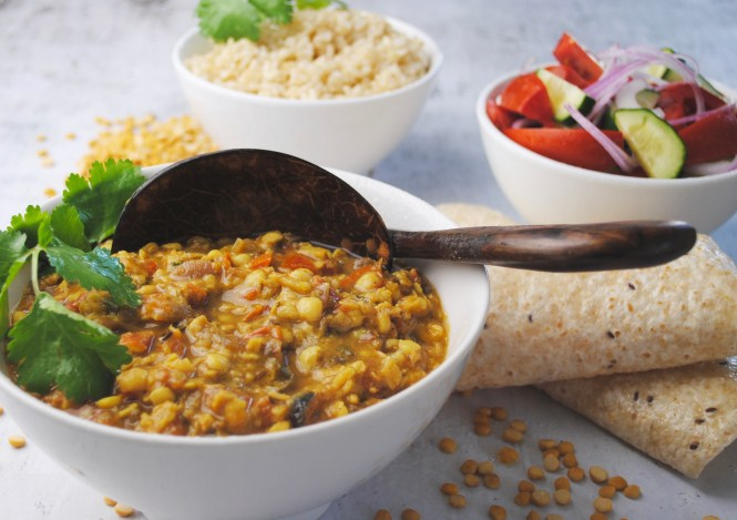 Spicy chana dal served in a white bowl with rice, salad and breads