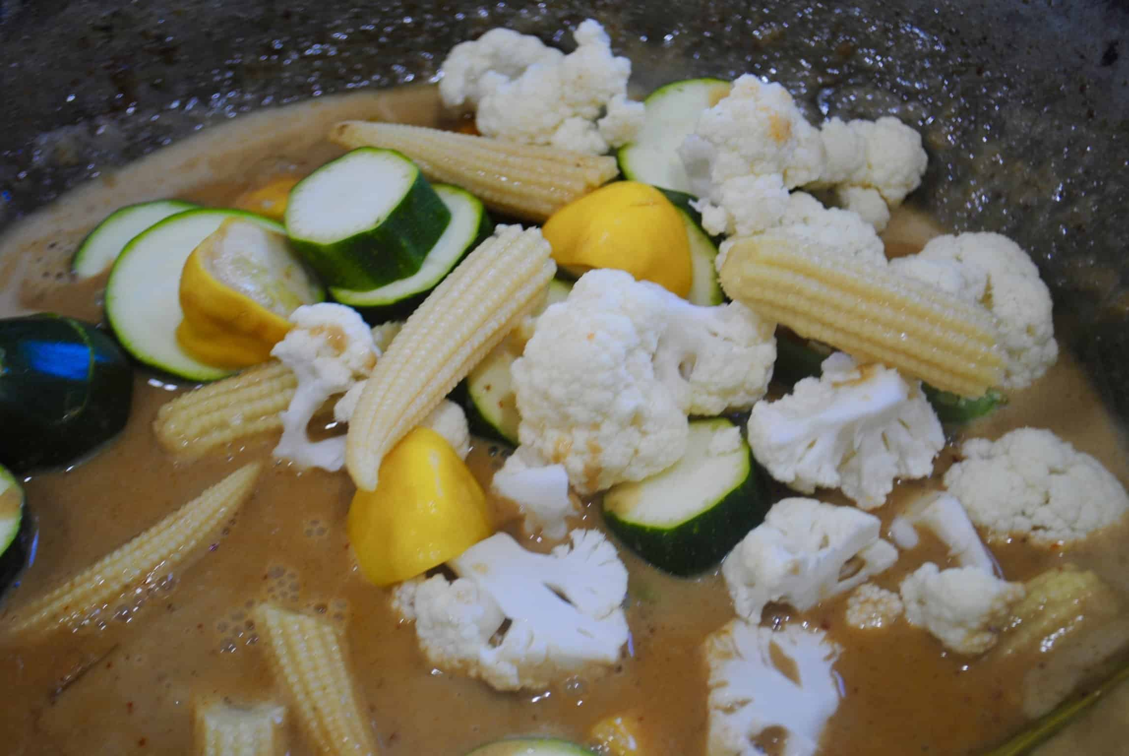 Thai vegetable red curry after the corn cauliflower zucchini and squash have been added