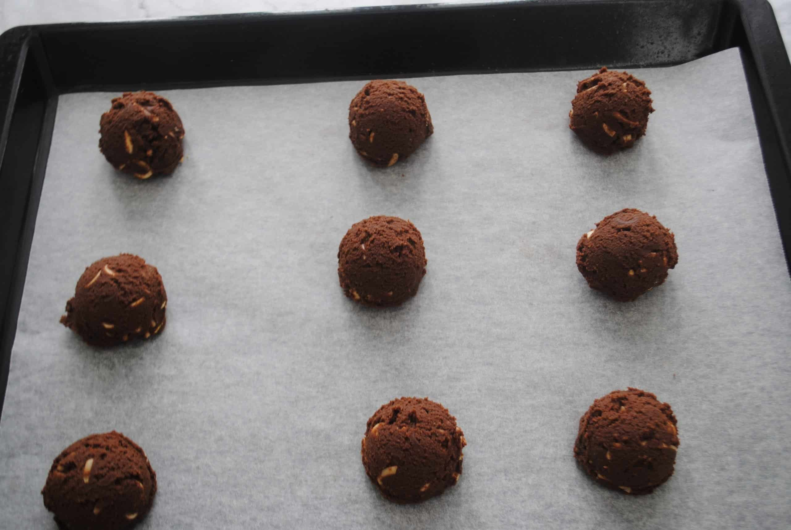 double chocolate almond cookies scooped into balls on baking paper on a baking tray