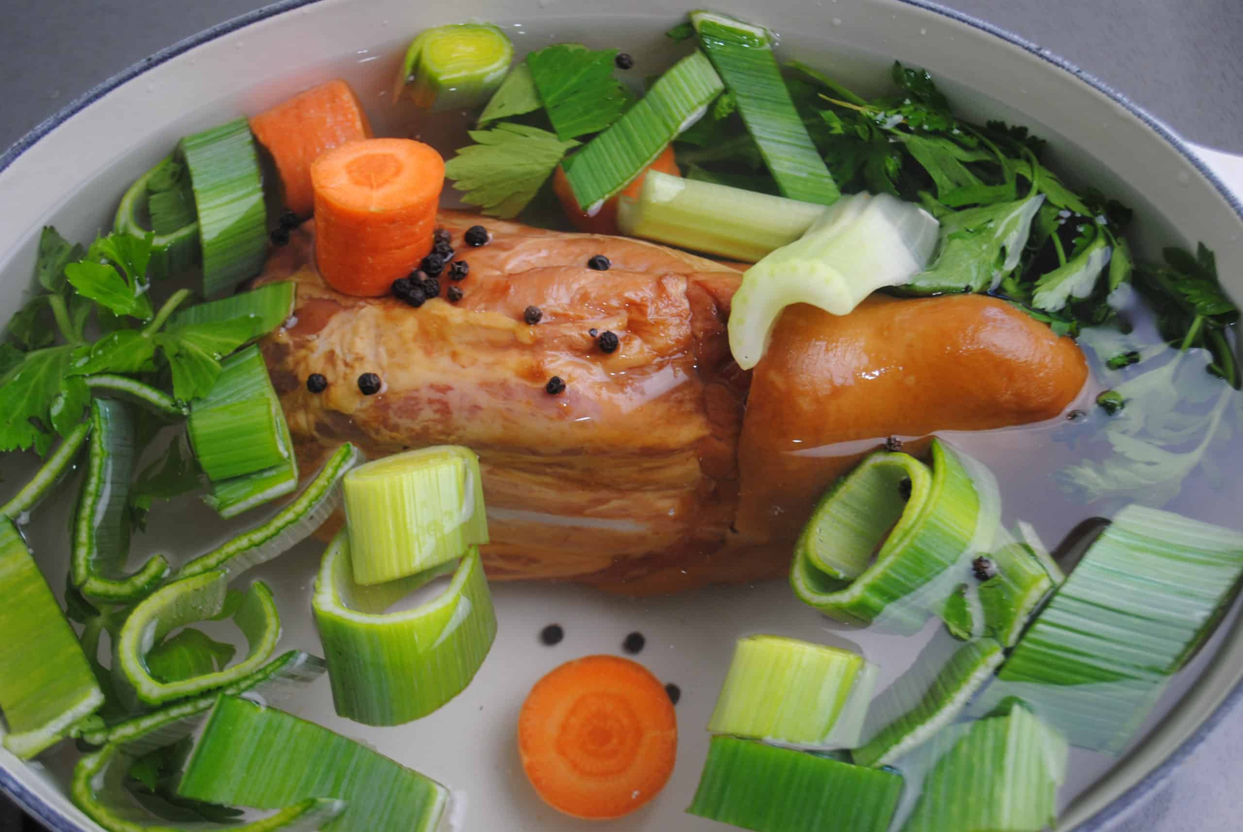 ham hock, carrot, leek, peppercorns and parsley in pot ready to cook pea and ham hock soup