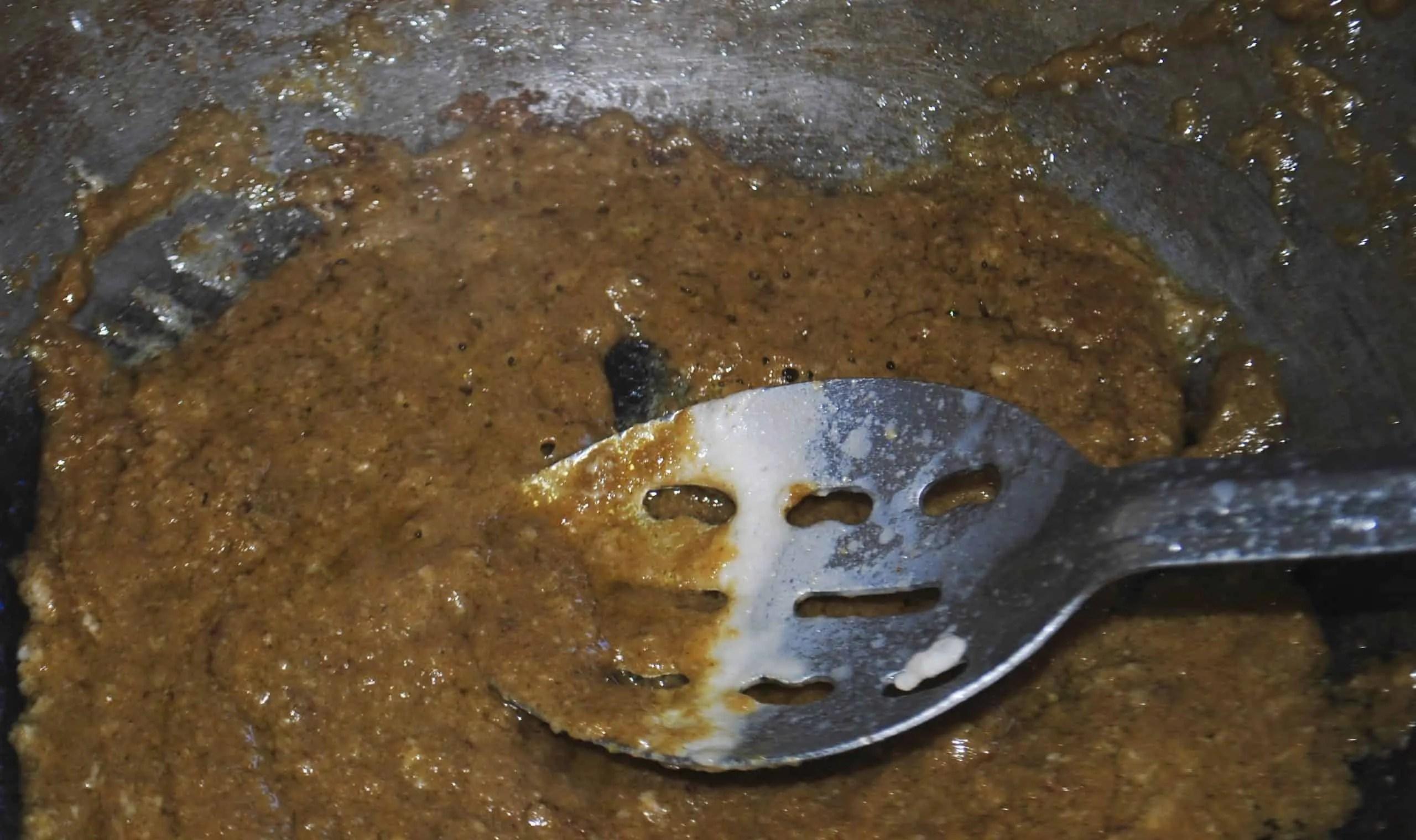 thai green chicken curry stirring curry paste through coconut cream in wok
