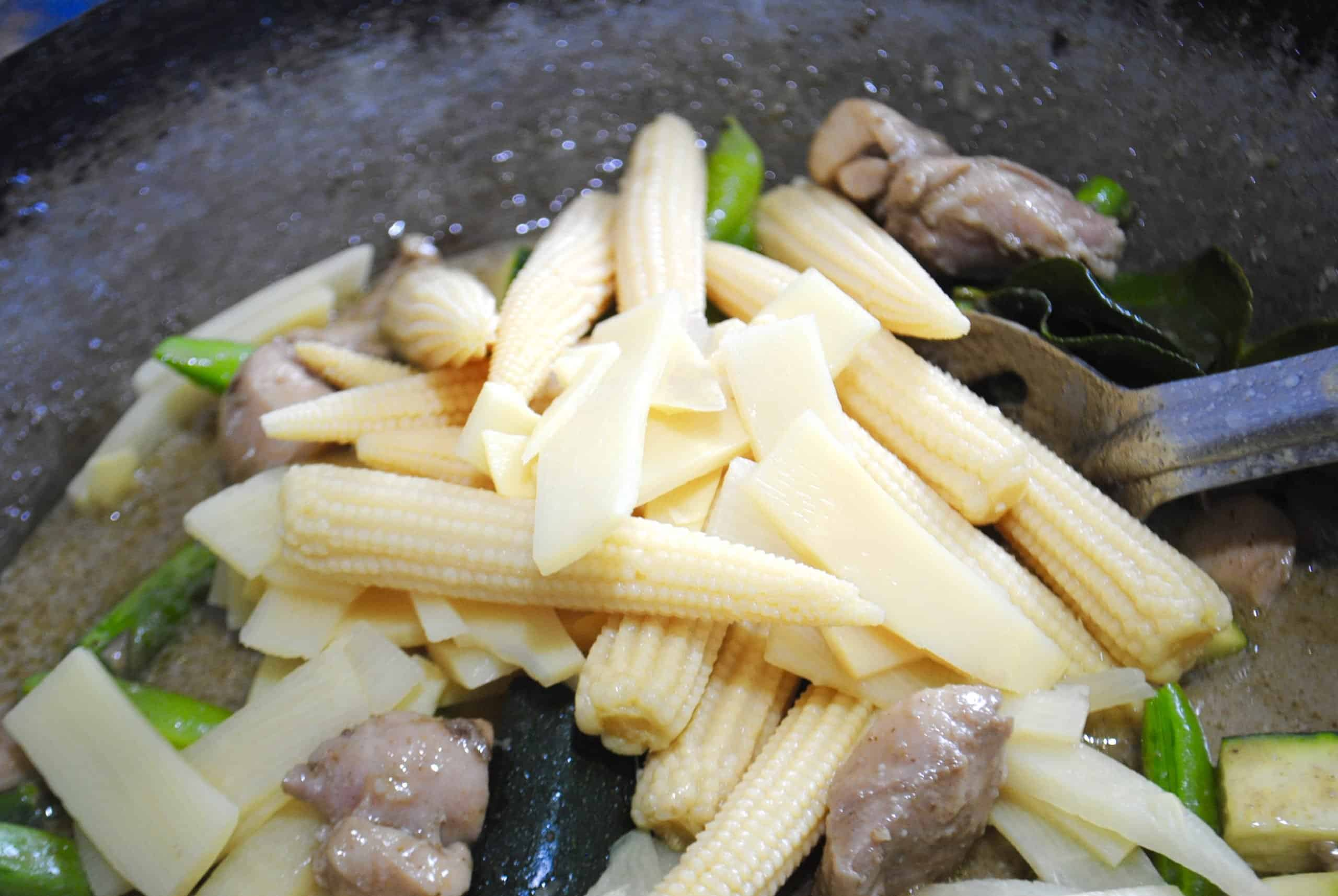 thai green chicken curry adding baby corn spears and bamboo shoots to curry in wok