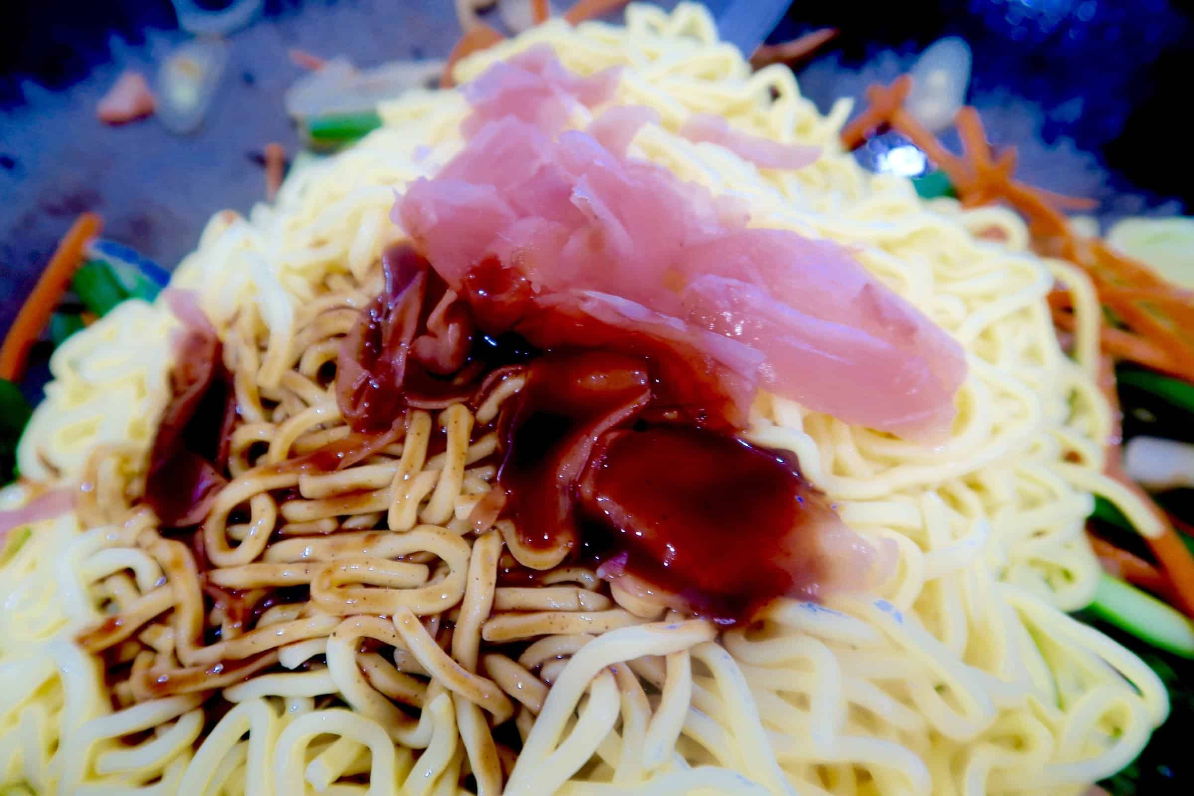 chicken yakisoba adding noodles, pickled ginger and sauce to wok